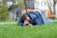 Photographer Takes a Shot on Green Grass. Photographer Takes a Shot on Grass Royalty Free Stock Photos