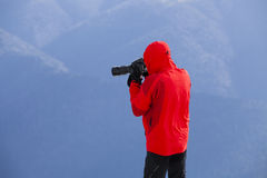 Photographer taking landscape pictures. Photographer taking beautiful outdoor pictures during a photo session in bucegi mountains, romania Royalty Free Stock Photography