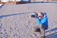 Photographer taking photo on beach Stock Photography