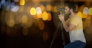 photographer taking a photo with the camera on the tripod. Blue and yellow bokeh background and boke Royalty Free Stock Photos