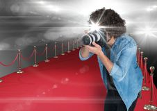 Photographer taking a photo with flash in the red carpet. Flares everywhere. Digital composite of photographer taking a photo with flash in the red carpet royalty free stock photo