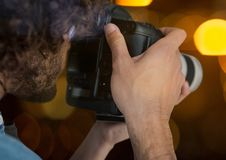 photographer taking a photo (foreground) in the city at night ( with blurred lights) Royalty Free Stock Images