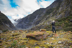 Photographer taking a photo in franz josef glacier in south island new zealand importanat natural traveling destination royalty free stock images