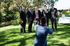 Photographer taking photo of groom and groomsmen Royalty Free Stock Image