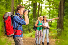 Photographer taking photo during hike. Young photographer taking photo during hike Royalty Free Stock Images