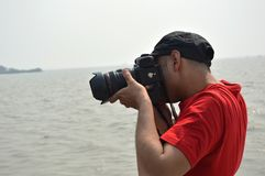 Photographer taking photo of nature Mumbai ocean. Photographer taking photo in holiday place Elephanta caves in Mumbai India. He is standing in boat in the mid Stock Image