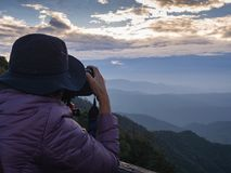 Photographer taking photo of landscape from top of the mountain Royalty Free Stock Image