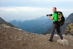 Photographer taking photo in the mountains Royalty Free Stock Photography