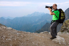 Photographer taking photo in the mountains Stock Image