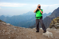 Photographer taking photo in the mountains Royalty Free Stock Photo