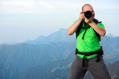 Photographer taking photo in the mountains Royalty Free Stock Images