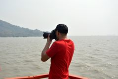 Photographer taking photo of nature Mumbai ocean. Photographer taking photo in holiday place Elephanta caves in Mumbai India. He is standing in boat in the mid Royalty Free Stock Image