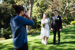 Photographer taking photo of newly married couple. In park royalty free stock photography