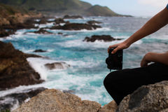 Photographer taking photo of ocean Stock Image