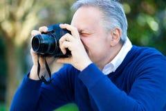 Photographer taking a photo outdoor. Stock Photos
