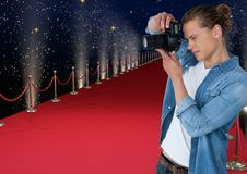 Photographer taking a photo  in the red carpet. Lights and stars back. Digital composite of photographer taking a photo  in the red carpet. Lights and stars back Royalty Free Stock Photography