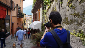 Photographer taking photo in Salita Serbelloni picturesque small town street view in Bellagio, Lake Como, Italy Stock Photo