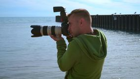 Photographer taking photo at sea beach. Close up of photographer with camera stock video