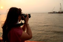 A photographer taking photo during the time of sunset in the sea water. She is enjoying sea water and taking pic of a ship. water is flowing slowly-slowly and Stock Images