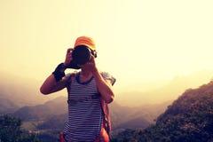 Photographer taking photo on top of mountain. Woman photographer taking photo on top of mountain Royalty Free Stock Photo