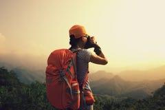 Photographer taking photo on top of mountain. Woman photographer taking photo on top of mountain Stock Image