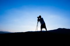 Photographer taking photograph. Photographer taking photo with camera and tripods blue sky background Stock Photo