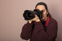 Photographer taking photos with a DSLR camera. Studio shot portrait of a young woman and professional photographer taking photos with a DSLR camera stock photography