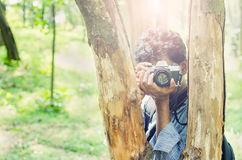 Photographer taking photos in forest. Photographer taking photos framing in between tree trunks with Film camera in natural outdoor, vintage look Stock Image
