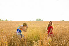 Photographer taking photos of girl model in a beautiful field.  Stock Photos