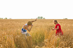 Photographer taking photos of girl model in a beautiful field.  Stock Photo