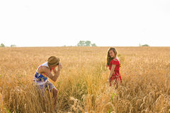 Photographer taking photos of girl model in a beautiful field.  Stock Photography