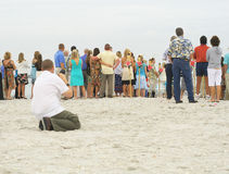 Photographer taking photos of group on beach Royalty Free Stock Image