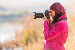 Photographer taking photos. Happy female photographer taking photos outdoors in fall Stock Images
