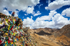 Photographer taking photos in Himalayas. Travel photographer taking photos in Himalayas mountains on cliff with Buddhist prayer flags. Leh, Ladakh, Jammu and Stock Images