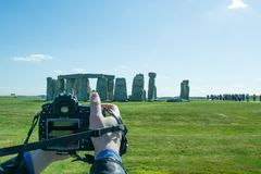 Photographer taking photos of the landscape. The path to Stonehenge - UNESCO World Heritage Site. Prehistoric monument that consists of a ring of standing Stock Images