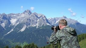 Photographer taking photos in the mountains stock video footage