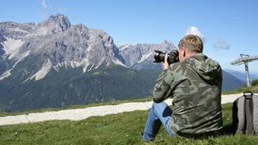 Photographer taking photos in the mountains. Nature photographer taking photos in the mountains stock footage