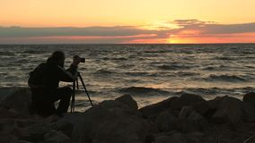 Photographer taking photos of seascape at sunset stock video footage