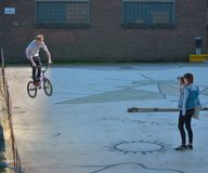 Photographer taking a picture of a boy jumping with his bike Royalty Free Stock Photography