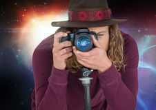 Photographer taking picture in colored lights background. Digital composite of Photographer taking picture in colored lights background Royalty Free Stock Photo