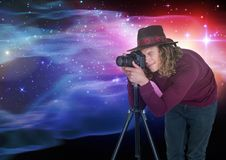 Photographer taking picture in front of colored lights background. Digital composite of Photographer taking picture in front of colored lights background Royalty Free Stock Images