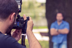 Photographer taking a picture of a man. In a park Royalty Free Stock Photography