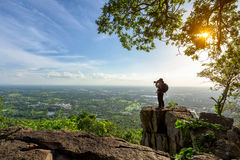Photographer. Is taking a picture of view of natural scenery on rock Royalty Free Stock Images