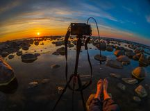 Photographer taking pictures of beautiful sunset at sea side. With stones at foreground Stock Images