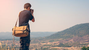 Photographer taking pictures. Closeup rear view of a photographer taking pictures on a mountain Royalty Free Stock Images