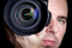 Photographer taking pictures with digital camera. Over black background Royalty Free Stock Images