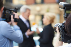Photographer Taking Pictures Of Female Journalist Interviewing B Royalty Free Stock Photos