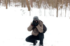 Photographer taking pictures in the forest in winter Stock Images