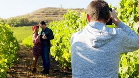 Photographer taking pictures of lovely couple in a vineyard. Shot in 6K on cinema camera stock video