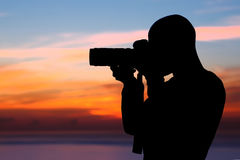 Photographer taking pictures outdoors. Photographer taking pictures, silhouette of a man with camera over beautiful orange sunset background, photographing stock photos
